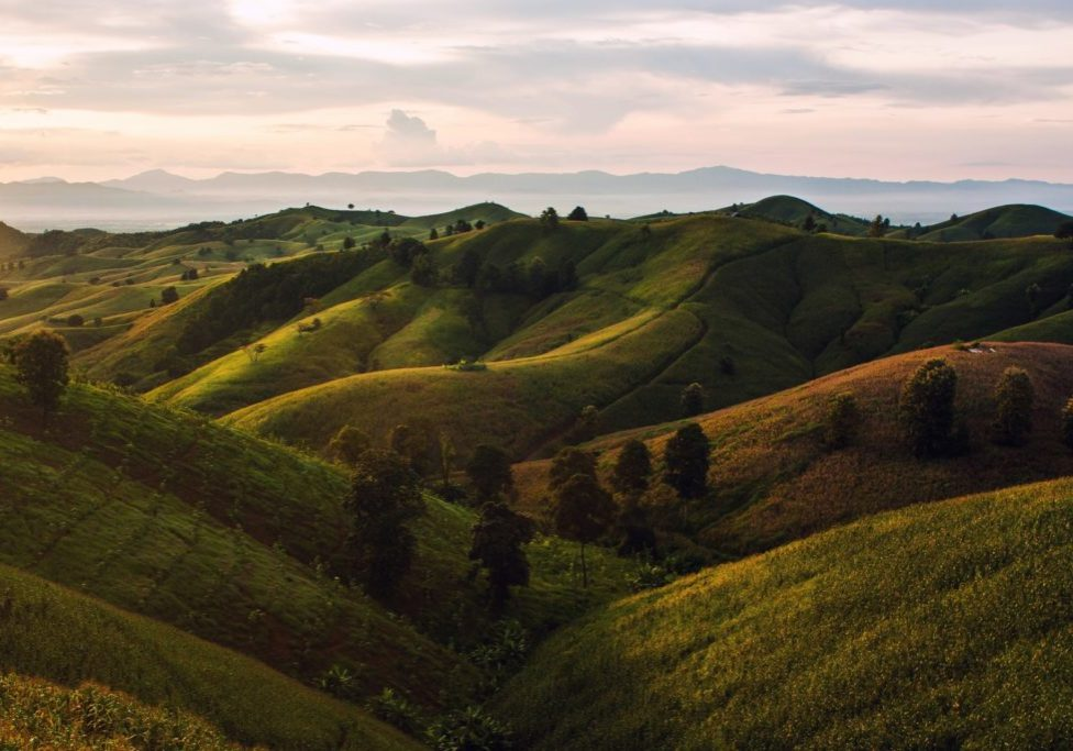 green rolling hills against a colorful sky