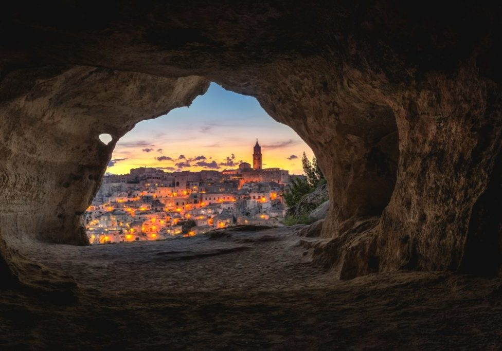 town illuminated through a cave opening