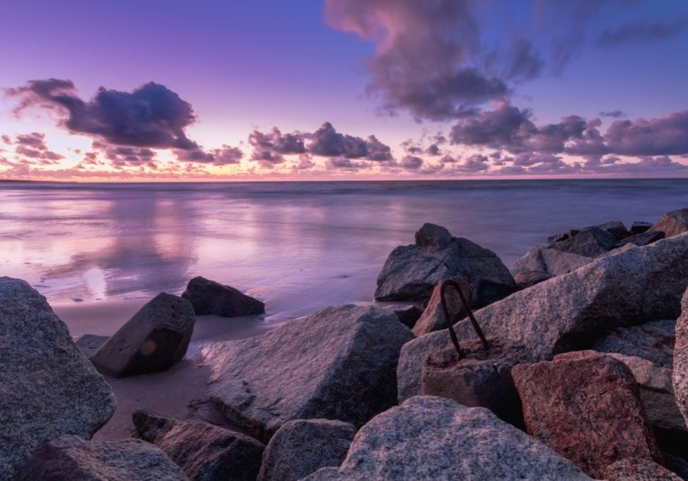 sunset over boulders and water lavender sky
